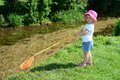 Young child fishing in a river girl toddler holding rod and net whilst standing on the bank of stream she is wearing pink hat Royalty Free Stock Photo