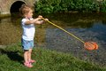 Young child fishing in a river girl toddler holding rod and net whilst standing on the bank of stream she is wearing white t shirt Royalty Free Stock Photo