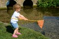 Young child fishing in a river girl toddler holding rod and net whilst standing on the bank of stream she is wearing white t shirt Stock Image