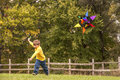 Young child flying kite little boy in a yellow shirt running and a colorful Stock Image