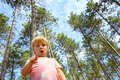Young child in forest pointing at camera a is standing outside the front of towering pine trees and a cloudy blue sky down the Stock Images
