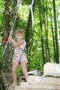 Young child girl in adventure park in safety equipment happy Royalty Free Stock Photo