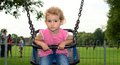 Young child girl playing on a swing at the playground toddler is in park she is wearing pink top and blue jeans and has blonde Royalty Free Stock Image
