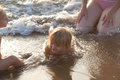 Young child girl playing with water at beach shore with brother and mum.Warm sunset light. Family summer travel Royalty Free Stock Photo