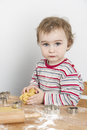 Young child making cookies vertical image of year old biscuit at wooden desk Stock Image