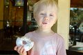 Young child making funny face while eating a doughnut is sitting outside coffee shop powdered sugar and Stock Image