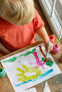 Young child painting picture a creative can be seen from above a happy of sun grass and trees on a piece of paper Stock Photography