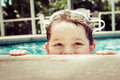 Young child peeking out of pool while swimming in vintage filtered image Stock Images