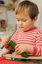 Young child peeling cucumber Stock Photo