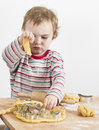 Young child playing with dough on wooden desk working flour vertical image Stock Photo