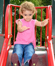 Young child playing on a slide at the playground girl toddler in park she has blonde curly hair and is wearing pink top and blue Royalty Free Stock Photo