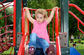 Young child playing on a slide at the playground girl toddler in park she has blonde curly hair and is wearing pink top and blue Stock Photos