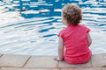 Young child pool water safety girl in red top sits seated by swimming side photo image from rear unidentified Stock Photos