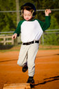 Young child running bases while playing baseball Stock Image
