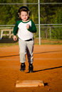 Young child running bases while playing baseball Stock Photo