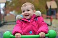 Young child smiling playing on a see saw at the girl toddler laughing as bounces up and down green park she is wearing bright pink Stock Photos