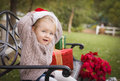 Young child wearing santa hat sitting with christmas gifts outsi outside Royalty Free Stock Images