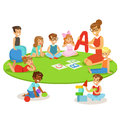 Young Children Learning Alphabet And Playing In Nursery School With Teacher Sitting And Laying On The Floor
