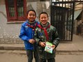 Young chinese students with a school book wearing student red scarfs standing in a hutong neighborhood Royalty Free Stock Photos