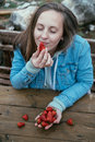 Young closed eyes woman eating strawberries in the nature on a b Royalty Free Stock Photo