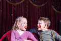 Young clowns sticking tongues out at each other boy and girl wearing clown make up sitting in chairs side by side and Royalty Free Stock Image