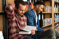 Young concentrated two african men reading books using laptop Royalty Free Stock Photo