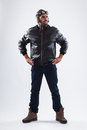 Young confident biker photo of a standing wearing leather jacket looking isolated on white Stock Photo