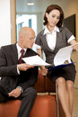 Young confident boss and his secretary looking on documents Royalty Free Stock Photography