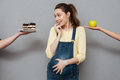 Young confused pregnant woman choosing between apple and cream cake