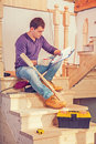 Young construction contractor sitting on wooden ladder holding c Royalty Free Stock Photo
