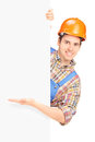 Young construction worker with helmet posing and gesturing on a panel isolated on white background Stock Photos