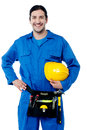 Young construction worker posing confidently happy holding safety helmet Stock Photos