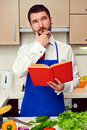 Young cook with cookbook thinking about recipe Royalty Free Stock Photography
