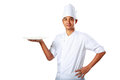 Young cook keeps an empty plate with thumb up isolated over white Royalty Free Stock Image