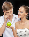 Young couple with apple portrait of beautiful smiling brunette girl giving to confused happy guy on black Stock Photo