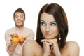 Young couple with apple portrait of beautiful smiling brunette men giving to confused happy woman Stock Photo