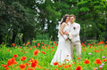 Young couple in the area of red poppies in the park. Royalty Free Stock Photo