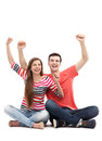 Young couple with arms raised sitting over white background Royalty Free Stock Photography