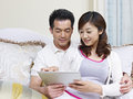 Young couple asian looking at tablet computer on couch Royalty Free Stock Image