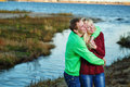 Young couple on banks of river tenderly and lovingly embrace each other Royalty Free Stock Image