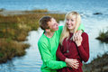 Young couple on banks of river tenderly and lovingly embrace each other Stock Photography