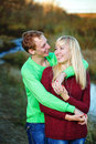 Young couple on banks of river tenderly and lovingly embrace each other Stock Photo