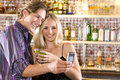 Young couple at bar with drinks taking photograph of themselves smiling Stock Photo