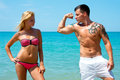 Young couple in the beach beautiful love having fun on man shows biceps woman Stock Photography