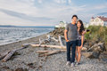 Young couple on beach with ferry and lighthouse cute asian american men arm around shoulder of woman standing in background copy Royalty Free Stock Photo
