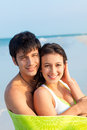 Young couple on beach medium shot of happy smiling latin wrapped in green towel ft Royalty Free Stock Photography