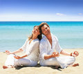 Young couple on beach, yoga Royalty Free Stock Photo