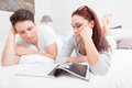 Young couple in bed reading magazine together lying Stock Photo