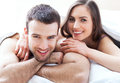 Young couple in bed under covers Royalty Free Stock Photo