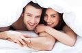 Young couple in bed under covers Royalty Free Stock Image